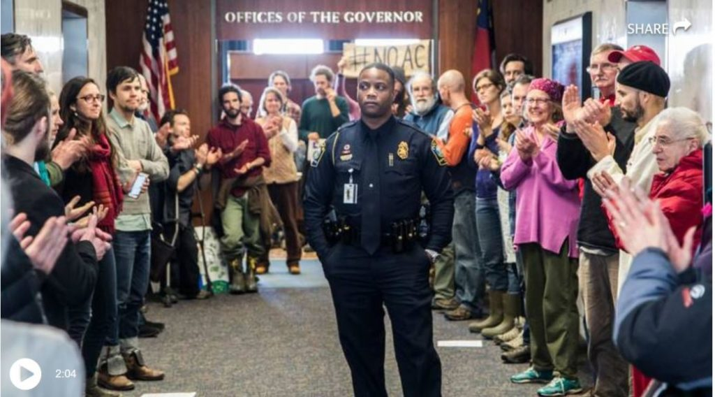 A police officer stands amid a protest outside NC Governors office