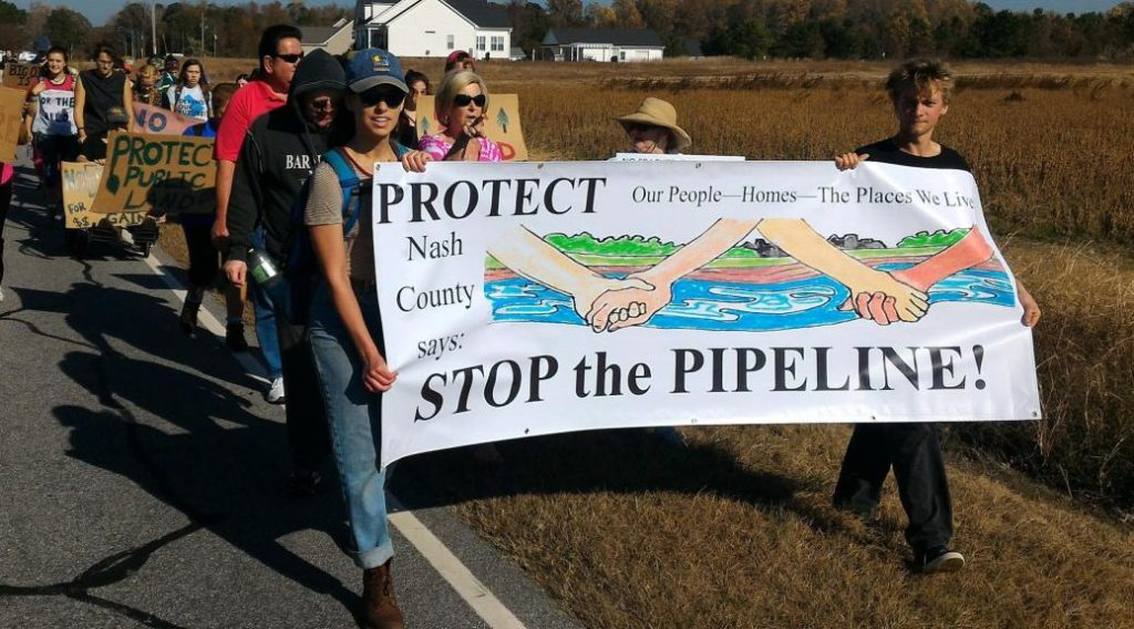 People march with a banner that says Protect our communities stop the pipeline